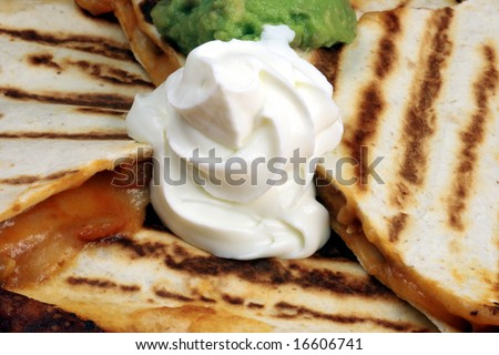 Mexican quesadilla made with cheddar, mozzarella cheese,beef   and fresh guacamole and sour cream