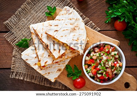 Mexican Quesadilla wrap with chicken, corn and sweet pepper and salsa. Top view