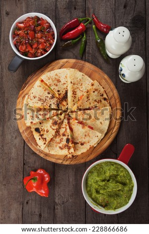 Mexican quesadillas with cheese, vegetables and guacamole dipping sauce - stock photo