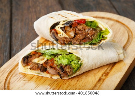 Mexican restaurant fast food - wrapped burritos with pork meat, mushrooms and vegetables closeup at wooden desk on table. Mexican burritos closeup. - stock photo