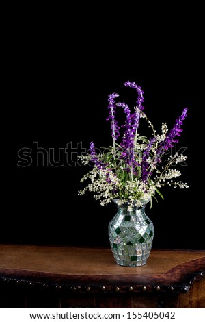 Mexican sage with silver lace flowers in a mosaic vase on a leather topped table isolated against a black background - stock photo