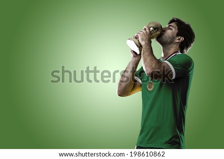 Mexican soccer player, celebrating the championship with a trophy in his hand. On a green background. - stock photo