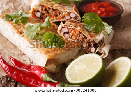 Mexican street food: chimichanga with minced meat close-up on the table. horizontal