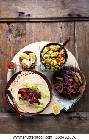mexican street tacos and Burritos with mushrooms, onions, guacamole. and beer. Comfort Mexican Food - stock photo