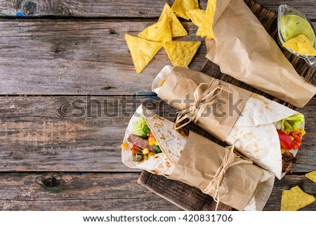 Mexican style dinner. Two papered tortillas with beef and vegetables served with nachos chips and guacomole sauce over old wooden background. Flat lay - stock photo