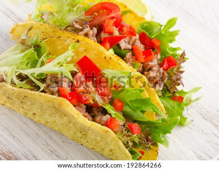 Mexican tacos on a wooden table. Selective focus