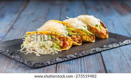 Mexican tacos with meat, beans, avocado, cheese and tomato sauce - stock photo