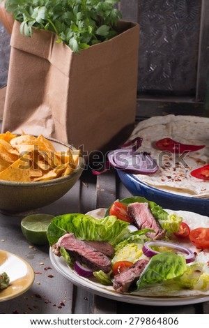 Mexican tortillas with green fresh salad filling, beef, onions, tomatoes with guacamole and tortilla chips on te vintage board - stock photo