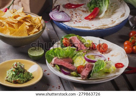 Mexican tortillas with green fresh salad filling, beef, onions, tomatoes with gucamole and tortilla chips on te vintage board - stock photo