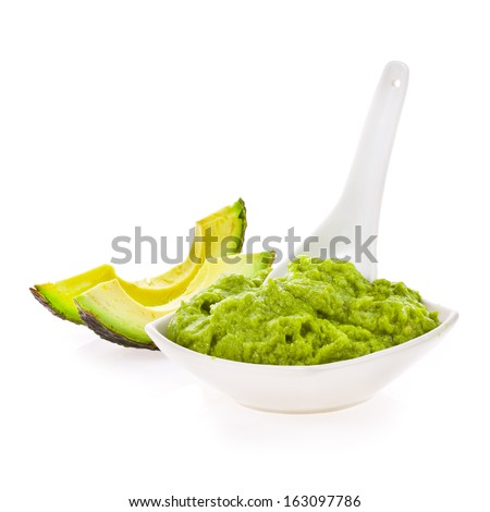 Mexican typical food  - Fresh guacamole in a white bowl with a spoon  isolated on white background - stock photo