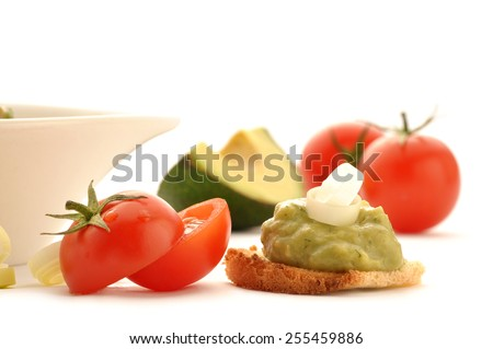 Mexican typical food - Fresh guacamole on whole grain rusk cherry tomatoes isolated on white background