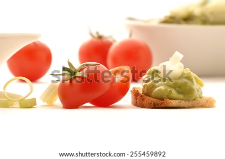Mexican typical food - Fresh guacamole on whole grain rusk cherry tomatoes isolated on white background - stock photo