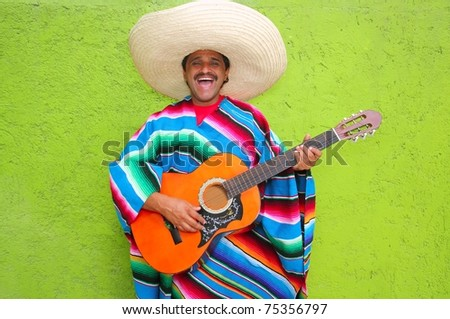 Mexican typical man playing guitar poncho on green wall - stock photo