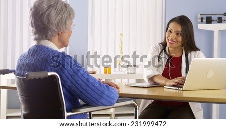 Mexican woman doctor talking with elderly patient