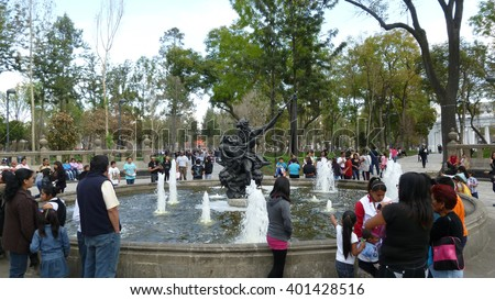 Mexico City, D.F, Mexico - December 2012: Mexicans and visitors gathered in the Alameda Central Park, around a fountain with a statue of Neptune.