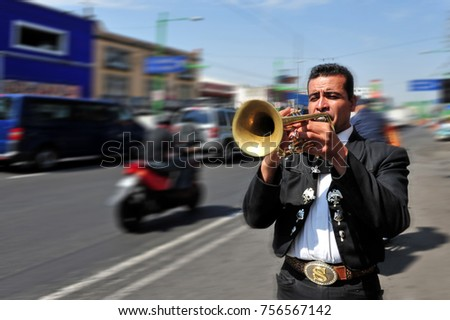 MEXICO CITY - FEB 24 2010 :Mariachi trumpet player plays a trumpet on a road near Plaza Garibaldi in Mexico City, Mexico. Mariachi is a Mexican musical tradition that dates back to the 19th century