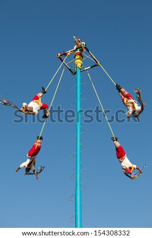 """MEXICO, RIVIERA MAYA, PLAYA DEL CARMEN - MARCH 4: Acrobat performers (Voladores) at """"Flying Men Dance"""" ceremony on March 4, 2013. The ritual in ancient times to please the God of rain. - stock photo"""