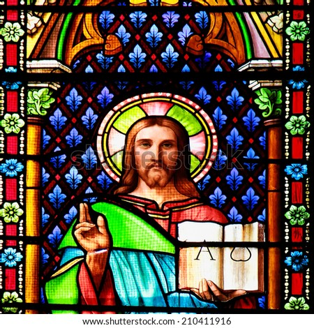 MEZE, FRANCE July 23, 2014: Jesus with the Bible. Stained glass window in the Cathedral of Meze, on July 23, 2014 in Meze, south of France - stock photo