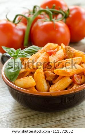 Mezze penne pasta with tomato sauce and pork sausage - stock photo