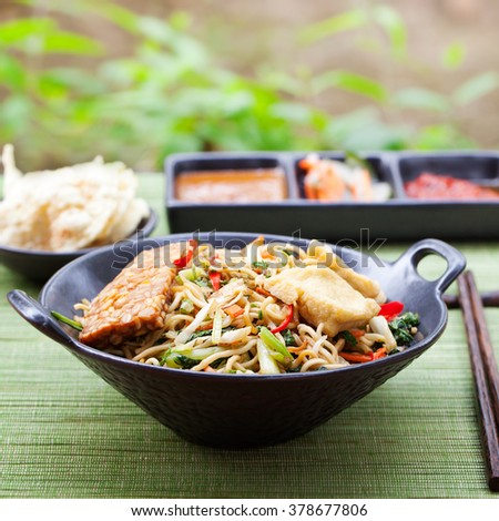 Mi goreng, mee goreng Indonesian cuisine, spicy stir fried noodles with tempeh and assortment of asian sauces Copy space - stock photo