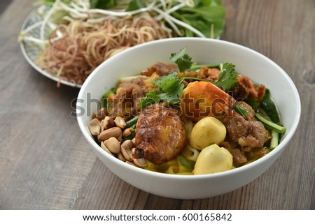 Mi Quang - Quang noodles which is cooked with shrimp, eggs and eaten along with peanut beans and vegetable.