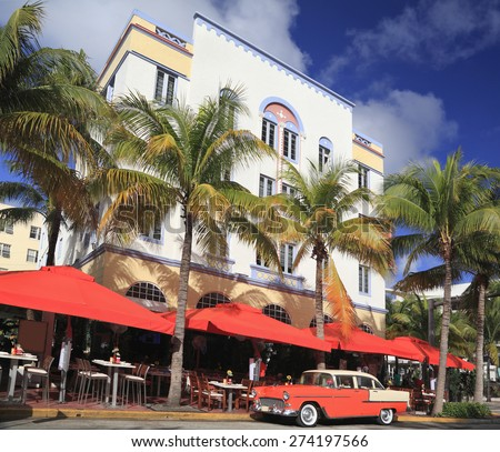 MIAMI BEACH, FL - DEC 30: Old car and restaurants on Ocean Drive, the major thoroughfare in the South Beach on Dec 30, 2014 in Miami Beach, FL, USA - stock photo