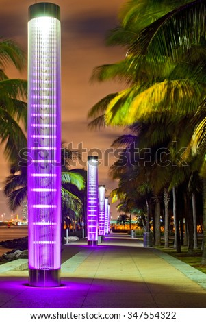 Miami BEach Florida at night, South Pointe park colorful lights and pedestrian path by the ocean and panorama of downtown in the background. Famous tourist destination. - stock photo