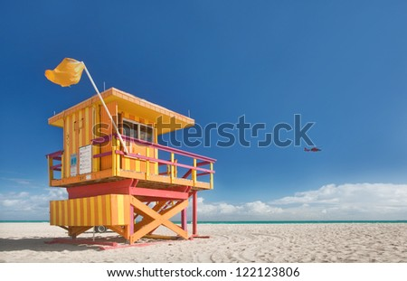 Miami Beach Florida, lifeguard house in a typical colorful Art Deco style on a bright sunny summer day, with blue sky and Atlantic Ocean in the background. World famous travel location. - stock photo