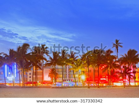 Miami Beach Florida, sunset over illuminated skyline of hotels and restaurants in art deco architectural style - stock photo