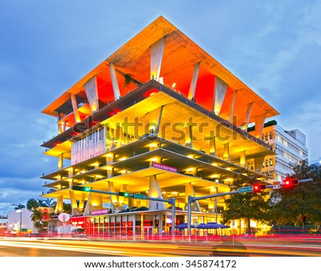 Miami Beach, Florida USA-November 13, 2015:Mixed use building, designed by famous architects Herzog & de Meuron in Lincoln Road, Miami, FL, shops, dining and parking. Sunset shot with moving traffic - stock photo