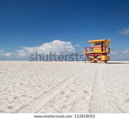 Miami Beach Florida, yellow lifeguard house in typical colorful Art Deco style on a sunny summer day, with blue sky and clouds. World famous travel location - stock photo