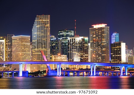 Miami city skyline closeup at dusk with urban skyscrapers and bridge over sea with reflection - stock photo
