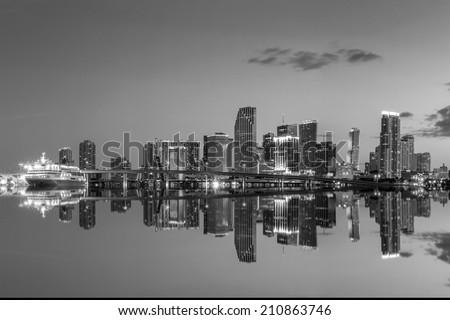Miami city skyline panorama at twilight with urban skyscrapers and bridge, black, white - stock photo