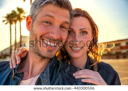 miami couple smiling for selfie - stock photo
