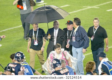 MIAMI - FEB 4: Singer Billy Joel (C) walks off the field after performing at Super Bowl XLI between the Indianapolis Colts and Chicago Bears at Dolphins Stadium on February 4, 2007 in Miami, Florida. - stock photo