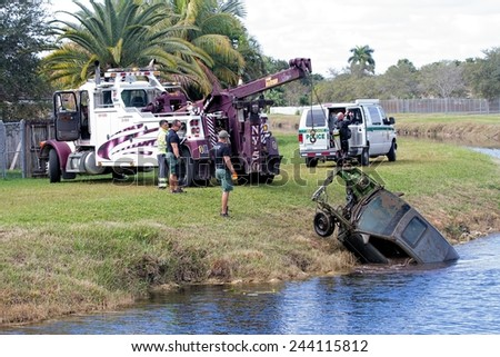 MIAMI, FLORIDA - DECEMBER 14, 2014: A Miami-Dade County Sheriff Department's Diving team retrieves a completely stripped and suspicious looking car from a canal in a residential neighborhood - stock photo
