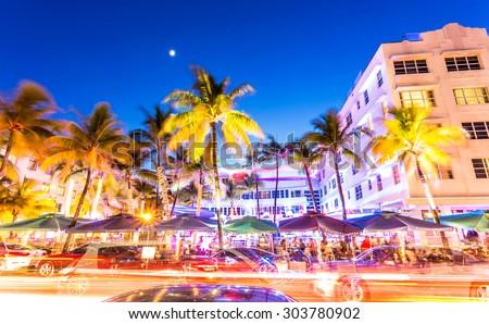 MIAMI, FLORIDA - JUNE 21, 2015: Cars speed down Ocean Drive. The road is the main thoroughfare through South Beach, Miami. Ocean Drive scene at night lights, cars and people having fun, Miami beach. - stock photo