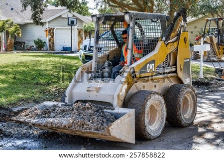 Miami, Florida - November 07, 2014:  A front loader working on a construction site in a residential neighborhood, improving the draining system for the wet rainy season