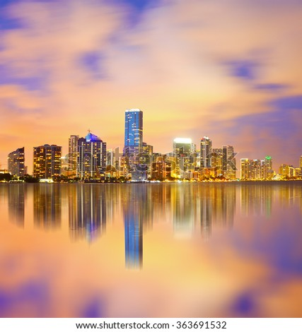 Miami Florida, sunset cityscape over the city panoramic skyline with lights on the modern downtown skyscraper buildings and Biscayne Bay water reflection