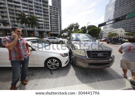 MIAMI - JULY 14: Car accident on Brickell Boulevard and 5th Street intersection at Brickell Miami July 14, 2015 in Miami FL USA. PErsons involved in this accident are standing by on the phone.  - stock photo