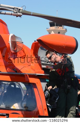 MIAMI - NOVEMBER 3: US Coast Guard pilot prepares his helicopter for flight on November 3, 2012 at Opa Locka airport in Miami, Florida - stock photo