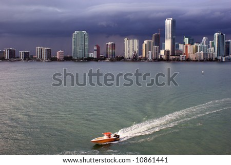 Miami skyline and Biscayne Bay with brightly colored power boat in foreground. - stock photo