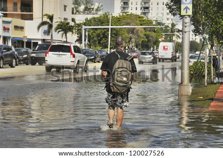 MIAMI - SOUTH BEACH - FLORIDA, OCTOBER 28: Man walk in Miami South beach Lenox Ave flood aftermath of Hurricane Sandy on october 28 2012 in Miami South Beach. - stock photo