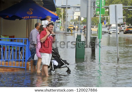MIAMI - SOUTH BEACH - FLORIDA, OCTOBER 28: People walk in Miami South beach Lenox Ave flood aftermath of Hurricane Sandy on october 28 2012 in Miami South Beach. - stock photo