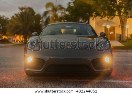 MIAMI, USA - APRIL 30, 2016: Full shot front view with headlamps on of a Porsche Cayman. Night scene on APRIL 30, 2016 in Miami, USA.