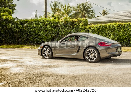 MIAMI, USA - APRIL 30, 2016: Long shot of a young man driving a Porsche Cayman. Urban scene on APRIL 30, 2016 in Miami, USA.
