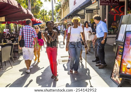 MIAMI, USA - AUG 1, 2013: people go shopping in the afternoon sun in Lincoln Road, Miami, USA. Lincoln Road Mall is a pedestrian-only promenade and the epicenter of whats happening in South Beach. - stock photo