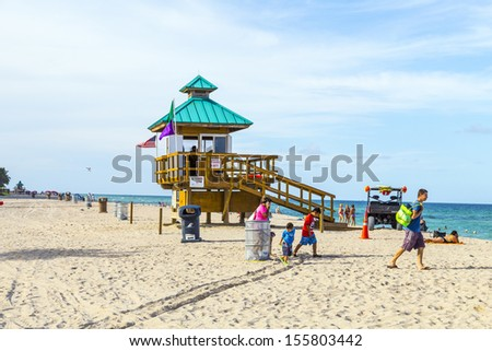 MIAMI, USA - JULY 29: people relax at Sunny Isles protected by guards in lifeguards huts on July 29, 2013 in Miami, USA. Harvey Graves purchased the  land 1920 for development as tourist resort.