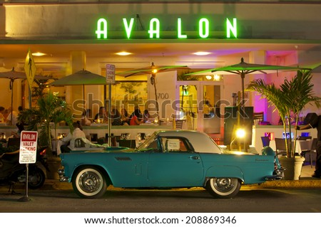 MIAMI, USA - JUNE 7, 2012: The Art Deco Avalon Hotel and a classic car at night on Ocean Drive. South Beach, Miami, Florida, United States of America, june 7 2012 - stock photo
