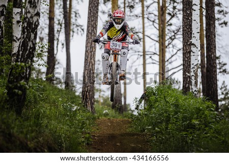 "Miass, Russia - May 29, 2016: athlete racer bike jump with a mountain in forest on helmet video camera during Cup ""Ryder"" downhill - stock photo"